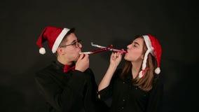 Portret para w Santa kapeluszach, dmuchają w drymbie gwizd na nowym roku zbiory