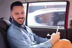 Portret pasażerski faceta mienia smartphone i patrzeć przychodził obrazy stock