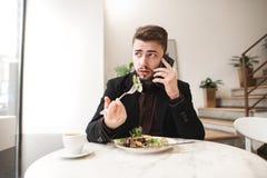 Portret patrzeje daleko od ruchliwie mężczyzna który opowiada na telefonie i je sałatki z rozwidleniem w wygodnej restauracji, zdjęcia stock