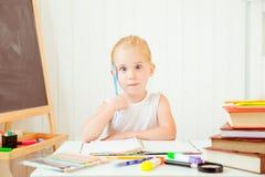 Portret patrzeje intrygujący rozważna mała dziewczynka podczas gdy robić pracie domowej zdjęcie stock