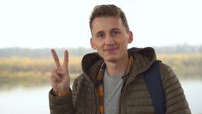 Portret patrzeje kamerę i pokazuje zwycięstwo znaka przystojny mężczyzna, zakończenie w górę, plenerowego w ranek naturze zbiory wideo