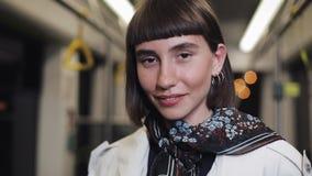 Portret patrzeje kamerę w tramwaju i ono uśmiecha się modniś młoda kobieta, steadycam strzał Zako?czenie zdjęcie wideo
