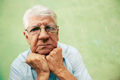 Portret patrzeje kamerę z rękami na podbródku poważny stary człowiek Zdjęcia Stock
