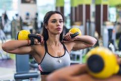 Portret patrzeje lustro dysponowana kobieta, ćwiczy z kettlebell w gym Obraz Royalty Free