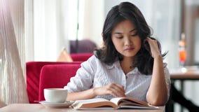 Portret peinzende elegante jonge vrouwelijke student die het goede boek van de tijdlezing hebben en koffie drinken stock videobeelden