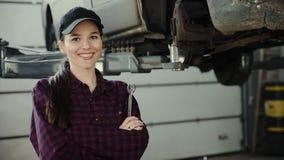Portret piękna dziewczyna, auto mechanik z wyrwaniem w ręce na tle samochód na dźwignięciu, zbiory wideo