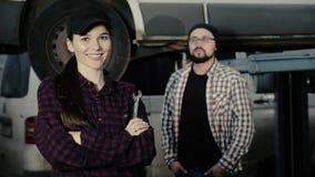 Portret piękna dziewczyna, samochodowy mechanik z spanner w jej rękach przeciw tłu mężczyzna, jej mentor zbiory wideo