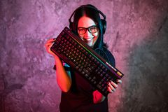 Portret Piękna Młoda Pro Gamer dziewczyny pozycja z i spojrzenia w kamerę hazard słuchawki i klawiaturą zdjęcie royalty free