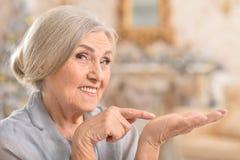 Portret piękna starsza kobieta patrzeje jej palmy zdjęcie stock