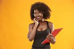 Portret piękna życzliwa amerykanin afrykańskiego pochodzenia kobieta z kędzierzawą afro fryzury i czerwieni falcówką fotografia stock