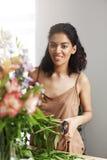 Portret piękna afrykańska dziewczyny kwiaciarnia ono uśmiecha się patrzejący kamerę robi kwiatu bukietowi Fotografia Stock
