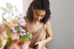 Portret piękna afrykańska dziewczyny kwiaciarnia ono uśmiecha się patrzejący kamerę robi kwiatu bukietowi Obraz Royalty Free