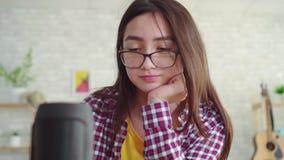 Portret piękna Azjatycka dziewczyna w szkłach z długie włosy w żywym izbowym nowożytnym czytaniu książka i cieszy się głos zbiory