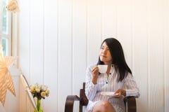 Portret piękna azjatykcia kobieta trzyma filiżankę herbaciany i patrzeje coś na okno w ranku w domu, Szczęśliwy i uśmiechnięty fotografia stock