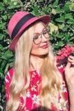 Portret Piękna blond dziewczyna w kapeluszu i szkłach Trzymać kwiatu w jego ręce na na wolnym powietrzu Za jej zielonym ulistnien obrazy stock