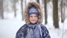 Portret piękna blondynki chłopiec w zima lesie z spada śniegiem zbiory wideo