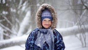 Portret piękna blondynki chłopiec w zima lesie z spada śniegiem - zwolnionego tempa wideo zbiory