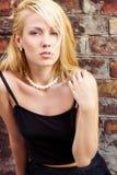 Portret piękna blondynki dziewczyna z niebieskimi oczami przeciw ścianie na ulicach miasto na letnim dniu zdjęcie royalty free