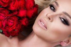 Portret piękna blondynki kobieta z długim blondynka włosy, perfect skóra, utrzymania twarz bukiet czerwone róże kwitnie dolinę Obrazy Stock