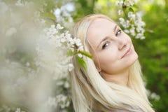 Portret piękna blondynki młoda kobieta wśród kwiatonośnych drzew zdjęcia royalty free