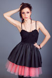 Portret piękna brunetki dziewczyna z krótkim włosy z czerwonymi kolczykami w czarnej sukni Fotografia Royalty Free