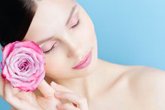 Portret piękna brunetki dziewczyna z różowi różanego na błękitnym tle Zdjęcia Stock