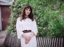 Portret piękna brunetki kobieta outdoors w białej sukni zdjęcia royalty free