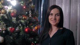 Portret Piękna brunetki kobieta W czerni sukni Blisko choinki zdjęcie wideo