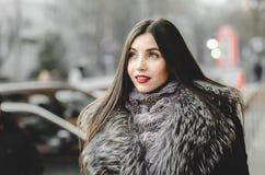 Portret piękna brunetki kobieta w futerku ma zabawę Obrazy Royalty Free