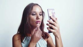 Portret piękna brunetki kobiety obrazu wargi glosa seksownymi wargami i patrzeć w małym lustrze w ręce uzupełnia zakończenie zdjęcie wideo