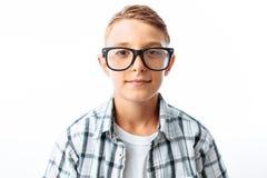 Portret piękna chłopiec z szkłami, nastoletni głupek ono uśmiecha się, w studiu na białym tle fotografia royalty free