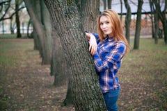 Portret piękna dziewczyna ono uśmiecha się, pozuje na kamerze w błękitnej koszula w klatce Przeciw tłu jesień Fotografia Royalty Free
