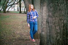 Portret piękna dziewczyna ono uśmiecha się, pozuje na kamerze w błękitnej koszula w klatce Przeciw tłu jesień Obraz Stock