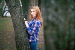 Portret piękna dziewczyna ono uśmiecha się, pozuje na kamerze w błękitnej koszula w klatce Przeciw tłu jesień Zdjęcia Royalty Free