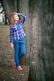 Portret piękna dziewczyna ono uśmiecha się, pozuje na kamerze w błękitnej koszula w klatce Przeciw tłu jesień Obrazy Royalty Free