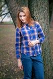 Portret piękna dziewczyna ono uśmiecha się, pozuje na kamerze w błękitnej koszula w klatce Przeciw tłu jesień Obraz Royalty Free