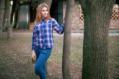 Portret piękna dziewczyna ono uśmiecha się, pozuje na kamerze w błękitnej koszula w klatce Przeciw tłu jesień Fotografia Stock