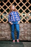 Portret piękna dziewczyna ono uśmiecha się, pozuje na kamerze w błękitnej koszula w klatce Na tło siatki Drewnianej siatce Obrazy Royalty Free
