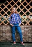 Portret piękna dziewczyna ono uśmiecha się, pozuje na kamerze w błękitnej koszula w klatce Na tło siatki Drewnianej siatce Obraz Royalty Free