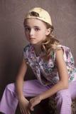 Portret piękna dziewczyna w koszulce i spodniach w przestawnym nakrętka pokoju uprzednio Zdjęcia Stock