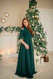 Portret piękna dziewczyna w zielonej wieczór sukni przy tłem drzewni boże narodzenia zdjęcie royalty free