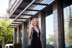 Portret piękna dziewczyna z długie włosy w przypadkowym stroju chodzi w mieście Piękna seksowna blondynki whith kawa i Fotografia Royalty Free