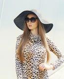 Portret piękna elegancka kobieta jest ubranym lampart suknię, słomianego kapelusz i okulary przeciwsłonecznych, Fotografia Royalty Free