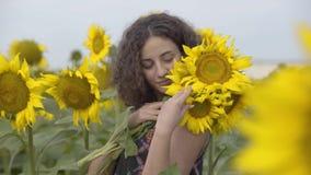 Portret piękna kędzierzawa dziewczyny pozycja na słonecznikowym polu z bukietem kwiaty Jaskrawy ? zdjęcie wideo