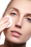 Portret piękna kobieta czyści jej twarz z kosmetycznym zwitkiem Piękna twarz młoda dorosła kobieta z czystą świeżą skórą Zdjęcia Royalty Free