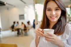 Portret piękna kobieta i trzymać filiżankę kawy w jej ręce na plamy tła sklep z kawą Fotografia Royalty Free
