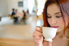 Portret piękna kobieta i trzymać filiżankę kawy w jej ręce na plamy tła sklep z kawą Zdjęcie Royalty Free
