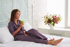 Portret piękna kobieta na białym łóżku z filiżanką herbaciany looki obrazy stock