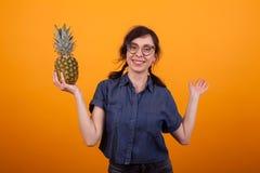 Portret piękna kobieta ono uśmiecha się przy kamerą i trzyma wyśmienicie ananas w studiu nad kolorem żółtym z szkłami zdjęcia stock