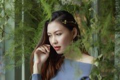 Portret piękna kobieta pod liści patrzeć obraz royalty free